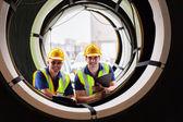 Warehouse workers standing between industrial tires — Stock Photo