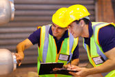Warehouse co-workers inspecting machinery — Stockfoto