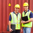 Shipping company workers standing in front of containers — Stock Photo