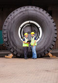 Warehouse workers standing in front of huge tire — Stock Photo