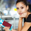 Pretty businesswoman with air ticket at airport — Stock Photo