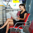 Young businesswoman reading newspaper at airport — Stock Photo