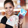 Young woman holding passport, air ticket and cash — Stock Photo