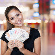 Young woman holding cash outside casino — Stock Photo
