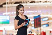 Podnikatelka na letišti číst své e-maily v tabletovém počítači — Stock fotografie