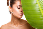 Beautiful woman face with green leaf — Stock Photo