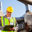 Petrochemical engineer recording technical data on clipboard — Stock Photo #27582445