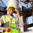 African oil chemical worker talking on cell phone — Stock Photo