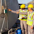Stock Photo: Industrial engineers inspecting fuel tank