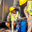 Petrochemical wokers inspecting pressure valves on fuel tank — Stock Photo #27585919