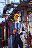 African industrial manager with binoculars in fuel refinery — Stock Photo