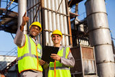 Fuel chemical workers at refinery plant — Stock Photo