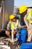 Petrochemical wokers inspecting pressure valves on fuel tank — Stock Photo