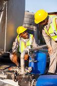Wokers pétrochimiques inspectant les valves de pression sur le réservoir de carburant — Photo