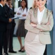 Businesswoman standing in office with colleagues on background — Stock Photo #27891493