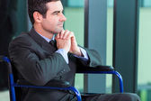 Handicapped businessman sitting in a wheelchair — Stock Photo