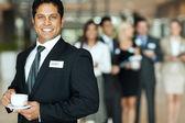 Indian businessman having coffee break during seminar — Stock Photo