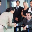 Businesswoman greeting handicapped business partner — Stock Photo