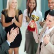Cheerful female corporate worker receiving a trophy — Stock Photo #28007669