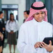 Stock Photo: Saudi arabibusinessmusing tablet computer