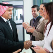 Stock Photo: Group of business team welcoming arabibusinessman
