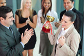 Cheerful female corporate worker receiving a trophy — Stock Photo