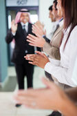 Business team applauding to welcome arabian businessman — Stock Photo