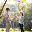 Teenage boy giving his girlfriend helium balloons — Stock Photo #28180853