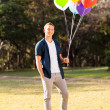 Teenage boy holding bunch of helium balloons — Stock Photo #28182013