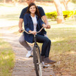 Teen couple riding a bike — Stok fotoğraf