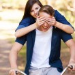 Teen girl covering boyfriend's eyes with hands on bike — Stock Photo