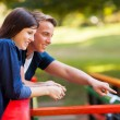 Teenage couple looking at a pond in the park — Stock Photo