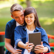 Stock Photo: Teenage couple taking self portrait outdoors