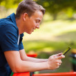 Cute teenage boy using tablet computer outdoors — Stock Photo #28184017