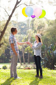Teenage boy giving his girlfriend helium balloons — Stock Photo