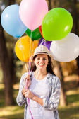 Teenage girl holding bunch of helium balloons — Stock Photo