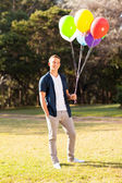 Teenage boy holding bunch of helium balloons — Stock Photo