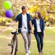 Cute teenage couple with bicycle outdoors — Stock Photo