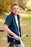 Smiling teenage boy with bike — Stock Photo