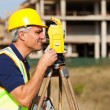 Stock Photo: Senior land surveyor working with theodolite