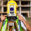 Stock Photo: Land surveyor looking through theodolite