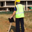 Rear view of land surveyor working at construction site — Stock Photo