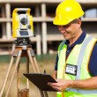Stock Photo: Mid age land surveyor working at construction site
