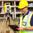 Foto Stock: Mid age land surveyor working at construction site