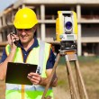 Stock Photo: Land surveyor talking on walkie talkie