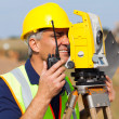 Foto Stock: Senior land surveyor working with tacheometer