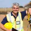 Stock Photo: Middle aged land surveyor outdoors