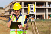 Land surveyor talking on walkie talkie — Stock Photo
