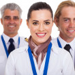 Flight attendant standing in front of pilots — Stock Photo #28704535