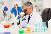Senior medical researcher looking through the microscope — Stock Photo